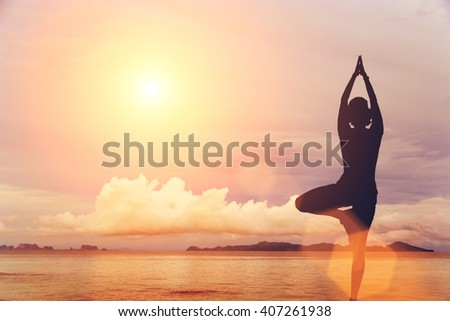 The woman is engaged in yoga on a background of rocks, the sea at blue sky. Toned - stock photo