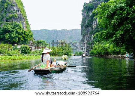 The woman is paddling groceries and fresh flowers boat. Tam Coc Grotto, Ninh Binh Province, Vietnam - stock photo