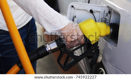 The woman is putting gas in her car.