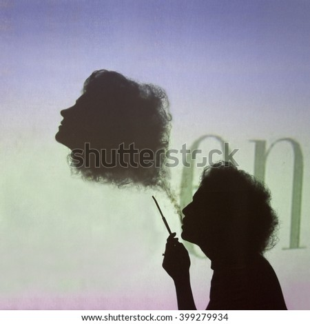 The woman is smoking and creating the abstract figure of the head from smoke similar to herself. A woman and her smoky copy have curly hair. This magic of smoke. Veil of two woman heads.  - stock photo