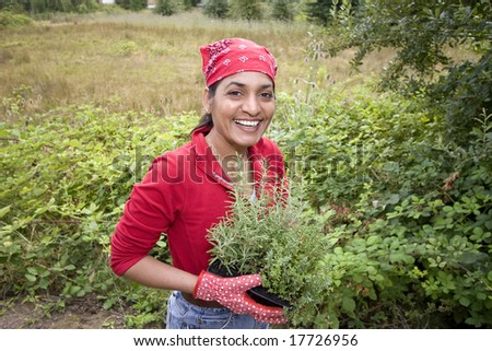 The woman is working in her garden.  She is getting ready to plant more plants in the garden.  Vertically framed shot. - stock photo