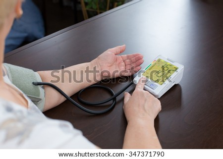 the woman measures to herself a blood pressure