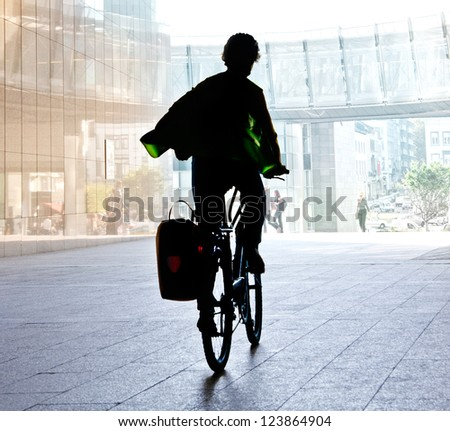 The woman on the bike after work. Urban scene. - stock photo