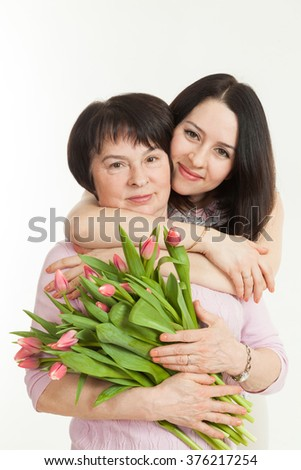 the woman presented a bouquet of flowers for mother and embraces her - stock photo