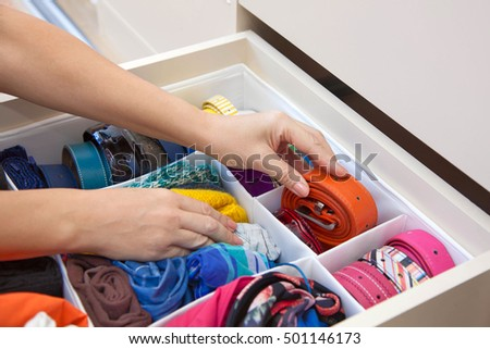 The woman pulls out a strap from a drawer of the wardrobe. Drawer with straps and belts.