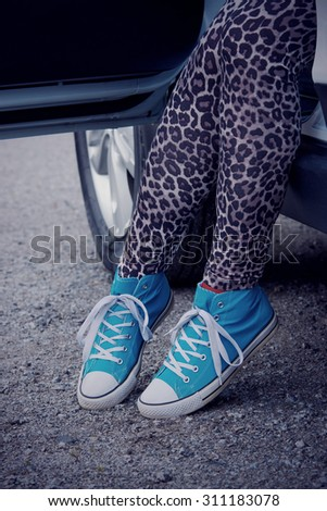 The woman rising out of the car with blue sneakers in Finland. She is wearing a leopard-print pants. Image includes a winter effect.