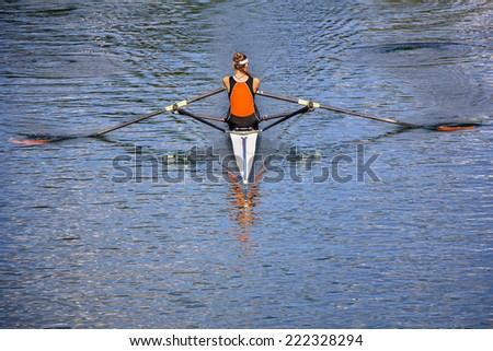 The woman rower in a boat, rowing on the tranquil lake  - stock photo