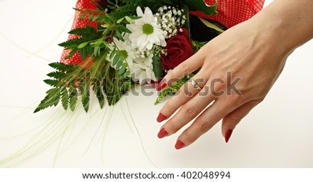the woman's finger is an engagement ring and a bouquet of flowers in the background