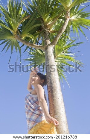 The woman screens her eyes from the sun while leaning against the palm tree under the clear sky
