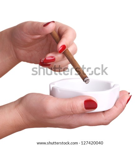 The woman shakes cigar ashes. Hands with beautiful manicure isolated on white background with cigar and ashtray - stock photo