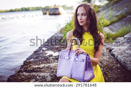 The woman sits on rocks with a handbag, waiting - stock photo