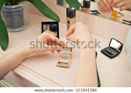 The woman takes earrings from a box sitting in front of the mirror. - stock photo