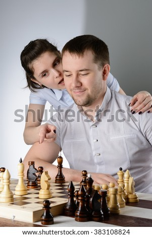 The woman tells the man's ear how to play chess - stock photo
