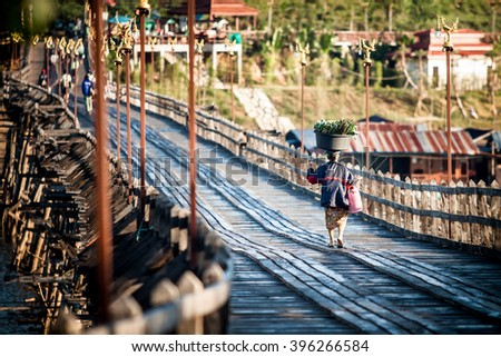 The woman took a basin on her head. Walking on a wooden bridge.