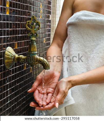 the woman touches water in the Turkish sauna - stock photo