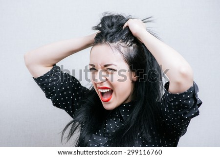 The woman was nervous, tearing their hair out. On a gray background. - stock photo