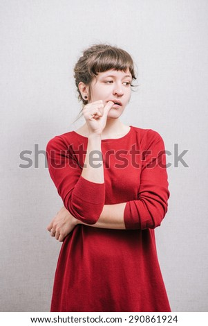 The woman was nervous, thinking with a finger in his mouth. On a gray background. - stock photo