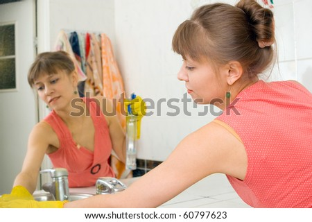 The woman washes a mirror in a bathroom - stock photo