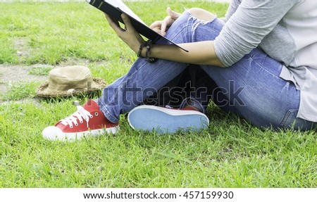The woman wear blue jean, wearing a red sneaker,put vice grip of a reading on the lawn. - stock photo