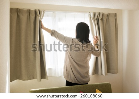 The woman who opens a curtain - stock photo