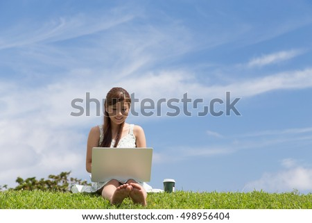 The woman who operates a personal computer in a park