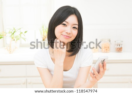 The woman who uses the smart phone in the kitchen