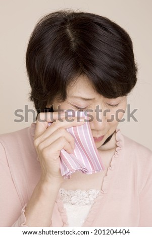 The woman wiping tears with a handkerchief