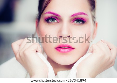 The woman with a bright pink make-up attentively looks forward. Studio portrait. - stock photo
