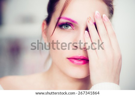 The woman with a bright pink make-up closes one eye a hand. Studio portrait. - stock photo