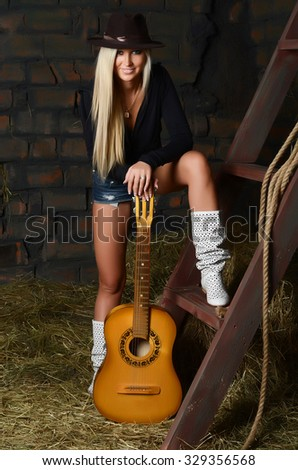 The woman with a guitar on hay - stock photo