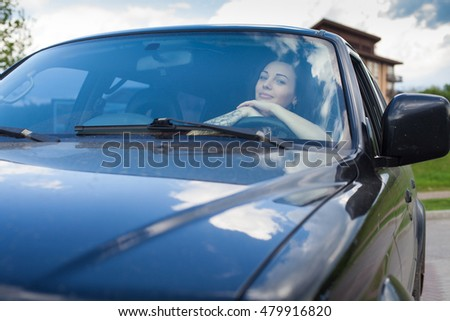 The woman with a tottoo is laying her hands on the wheel and looking on the road on the background of sky.