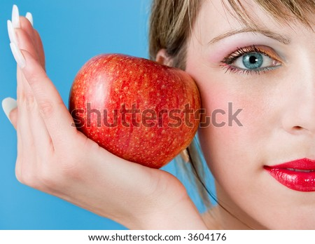 The woman with  appetizing apple on a blue background - stock photo