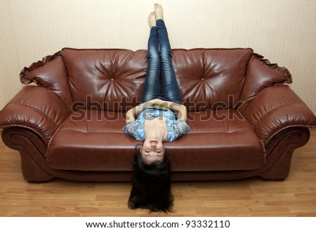 The woman with magazine lying in a room on a sofa