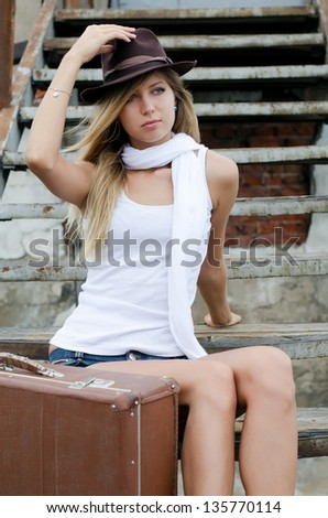 The woman with suitcase on old ladder - stock photo