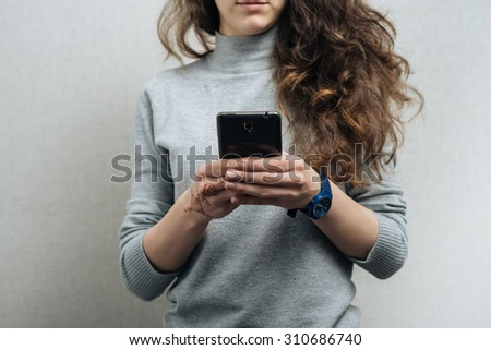 The woman with the phone. On a gray background. - stock photo