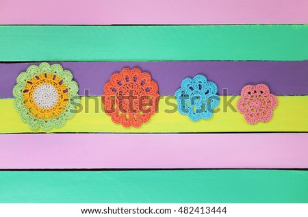 The wonderful  crochet doilies on colourful wooden table