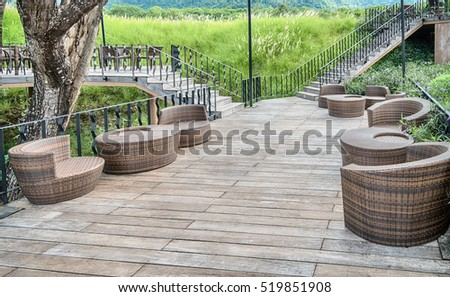 The wood table on natural outdoor of a restaurant with tree and cloudy sky
