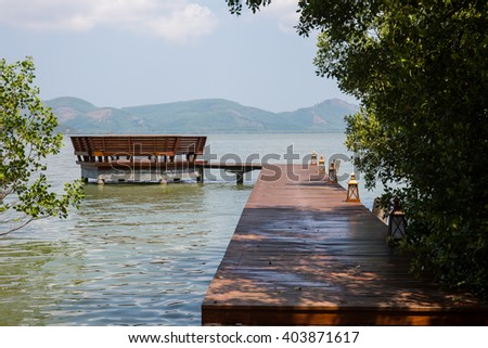 The wooden bridge landing to pavilion in the sea and mangrove rain forest