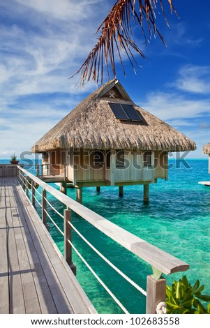 The wooden bridge to a hut over water at the ocean - stock photo