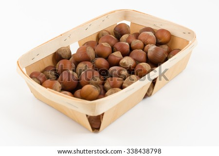 the wooden container is filled with hazelnut on a white background - stock photo