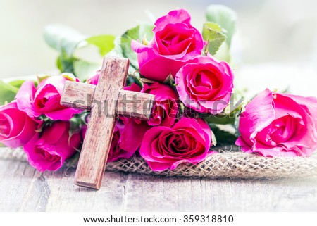 The wooden  cross and pink roses on wooden  background, burred background, concept, Valentine background - stock photo