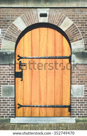 The wooden door in the brick house. Color is yellow with metallic accents. Doors leading to paving slabs.Above the door hangs a lantern. - stock photo