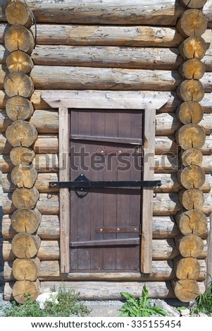 The wooden door in the wall of the log house