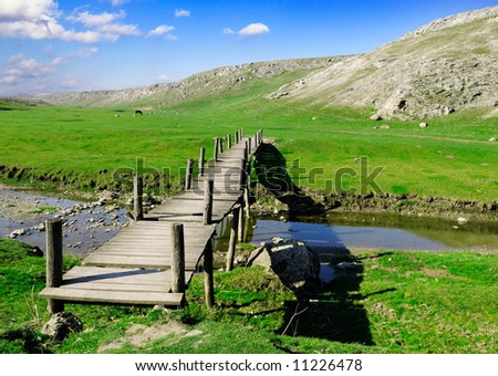 The wooden foot bridge and old mountains