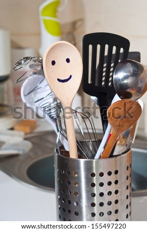 The wooden smiling spoon and kitchen accessories in the kitchen - stock photo