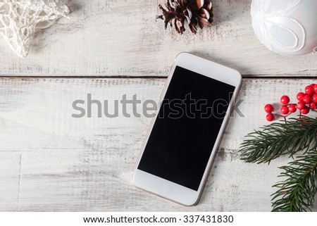 The wooden table with a phone and  Christmas decorations. Christmas mockup concept - stock photo