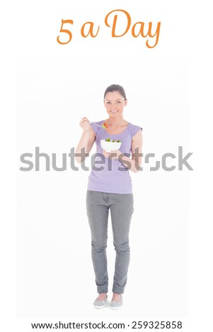 The word 5 a day against charming woman eating a bowl of salad while standing - stock photo
