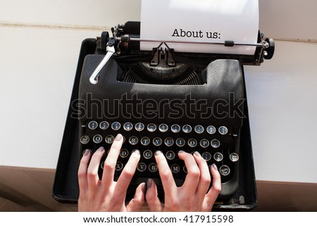 The word about us: against womans hand typing on typewriter - stock photo
