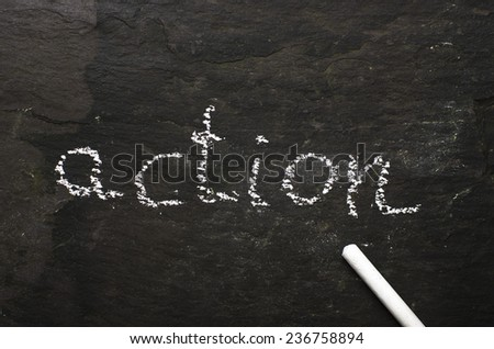 The word action written with chalk on black stone.