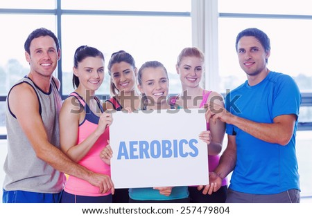 The word aerobics against portrait of a group of fitness class holding blank paper - stock photo